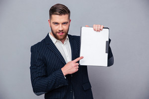 Handsome businessman showing blank clipboard