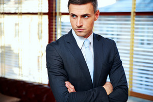 Handsome businessman with arms folded in office