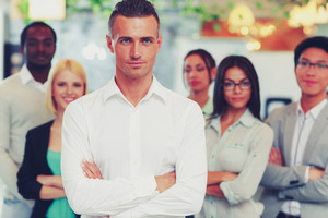 Handsome businessman with arms folded standing in front his colleagues
