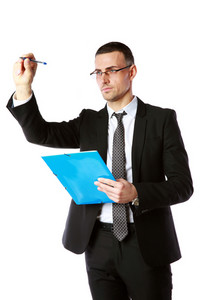 Handsome businessman writes with pen at copyspace over white background