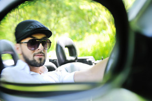 Handsome guy in a reflection of a side mirror