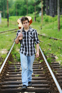 Handsome guy with guitar on a railroad