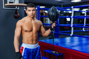 Handsome male boxer standing in gym and looking at camera
