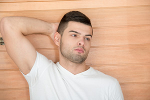 Handsome male model posing in front of a wooden background
