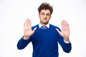 Handsome man showing stop gesture over white background