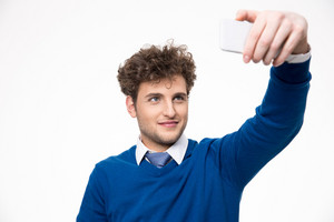 Handsome man taking selfie photo on smartphone over gray background