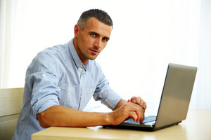 Handsome man using laptop at home