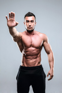 Handsome muscular man holding his palm out saying 'Stop' or 'No!'