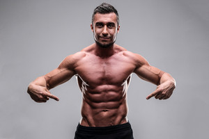 Handsome muscular man pointing at his abs over gray background