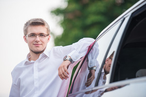 Handsome nicely dressed man posing by an elegant car