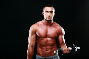 Handsome sexy sportsman working out with dumbbells over black background