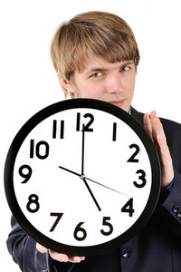 Handsome teenage huy holding clock in his hands