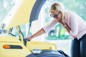 Handsome woman with glasses checking car engine