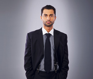 Handsome young executive in business suit standing in a studio