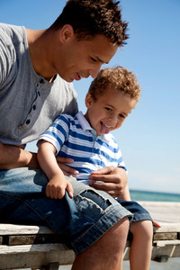Handsome young father enjoying summer with his little son against a bright background