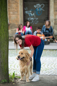 Handsome young girl posing petting a dog