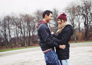 Handsome young man and beautiful woman standing together looking at each other smiling. Teenage mixed race couple in love in park.