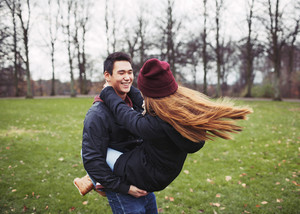 Handsome young man carrying his girlfriend in the park. Asian young couple enjoying themselves outdoors.
