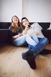 Handsome young man holding remote control changing channels sitting with his beautiful girlfriend laughing while watching television. Happy teenage couple relaxing together at home watching TV.