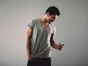 Handsome young man in casual t-shirt listening music on cell phone. Hispanic male model wearing earphones and listening to music through his smart phone on grey background.