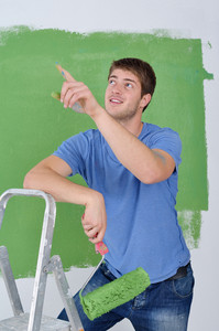 Handsome Young Man Paint White Wall In Color