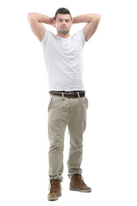 Handsome young man standing with his hands behind his head