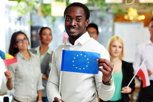 Happy african businessman holding flag of USA in front of colleagues