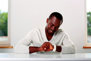 Happy african man sitting at the table and looking at wristwatch