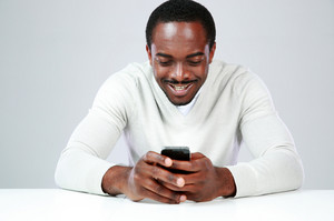 Happy african man sitting at the table and using smartphone