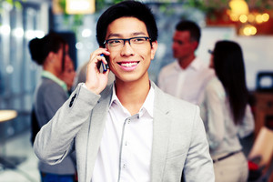 Happy asian businessman talking on the smartphone in front of colleagues