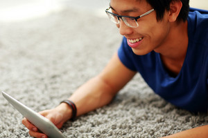 Happy asian man lying on the floor with tablet computer