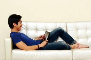 Happy asian man lying on the sofa with tablet computer at home