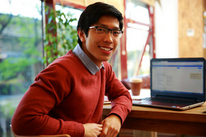 Happy asian man sitting at the table with laptop and looking at camera