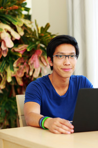 Happy asian man sitting at the table with laptop at home
