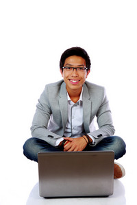 Happy asian man sitting on the floor with laptop