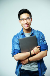 Happy asian man standing with laptop on gray background