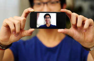 Happy asian man taking self picture with smartphone camera. Focus on smartphone