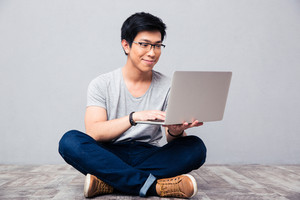 Happy asian man using laptop