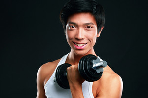 Happy asian man working out with dumbbells on black backgroung