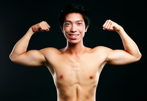 Happy asian muscular man with his arms stretched out on black background