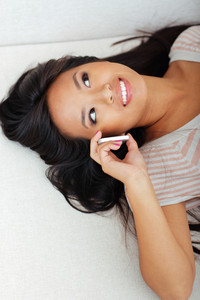 Happy asian woman lying on sofa while talking on phone