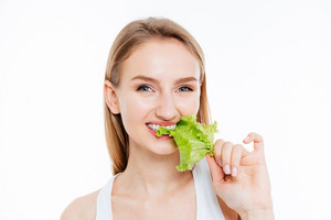 Happy attractive girl biting green salad isolated on a white background
