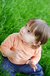 Happy baby boy sitting on the grass in meadow