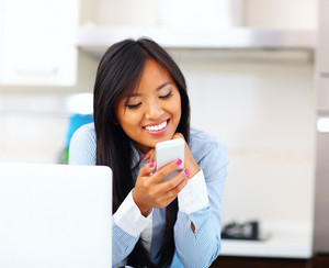 Happy beautiful asian businesswoman using smartphone