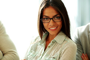 Happy beautiful businesswoman in glasses at office
