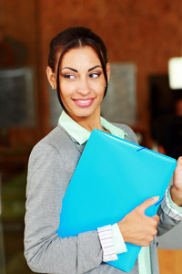 Happy beautiful businesswoman standing with folder in office