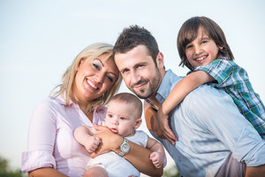 Happy beautiful family posing outdoors