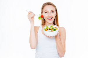 Happy beautiful woman eating fresh salad isolated on a white background