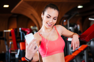 Happy beautiful young sportswoman listening to music and making selfie with smartphone in gym