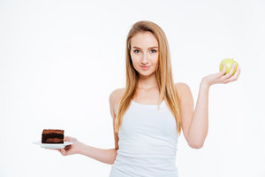 Happy beautiful young woman standing and holding chocolate cake and green apple over white background